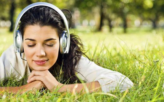 Обои Девушка с наслаждением слушает музыку в огромных наушниках