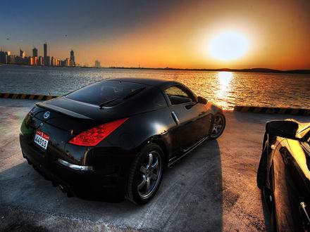 Обои Черный Nissan на закате припарнован на берегу моря