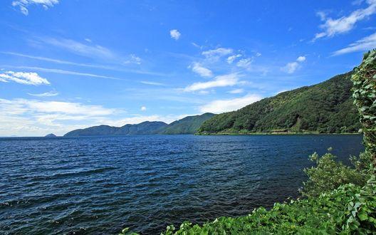 Обои Рябь на поверхности синего моря, окруженного зелеными холмами