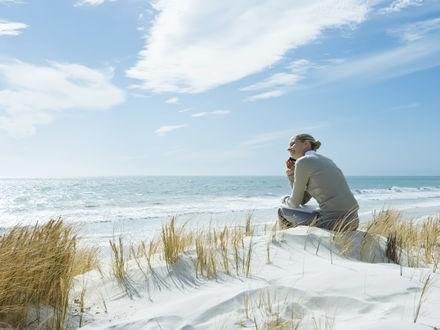 Обои Девушка говорит по мобильноиу телефону сидя на берегу океана