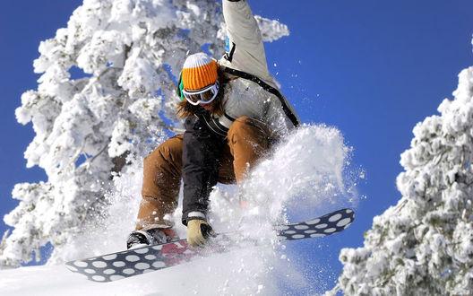 Обои Парень отдыхает в горах, катаясь на сноуборде