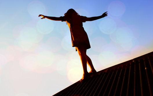 Обои Девушка балансирует на крыше дома