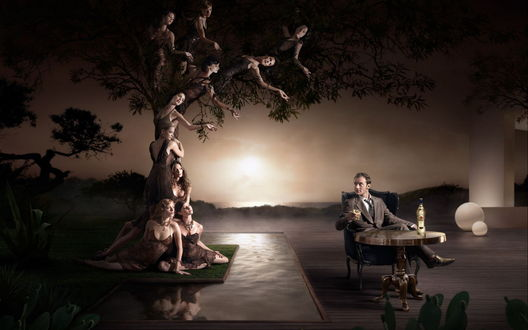 Обои Дерево из девушек рядом с мужчиной сидящим за столом и пьющим виски