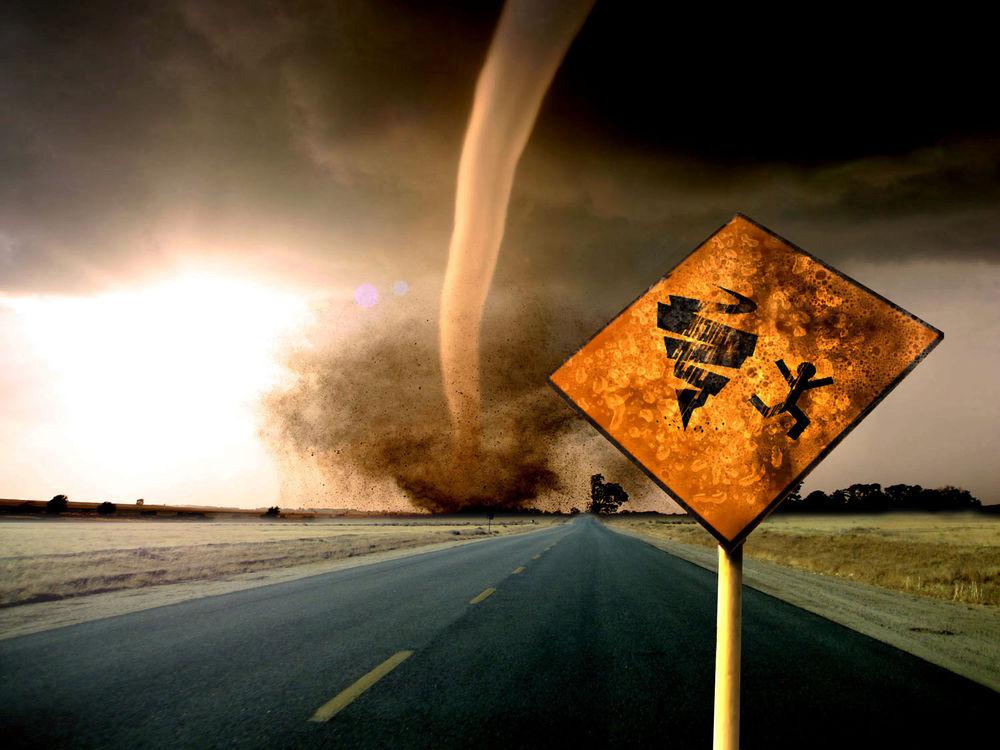 Обои для рабочего стола Торнадо движется вдоль дороги по направлению к знаку «Осторожно торнадо!»
