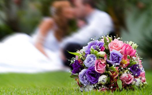 Обои Букет невесты на коротко подстриженном газоне на фоне целующихся жениха и невесты