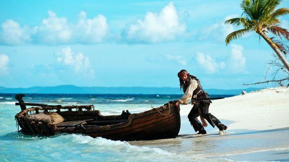 Обои Джек Воробей выталкивает лодку в море из фильма «Пираты карибского моря»