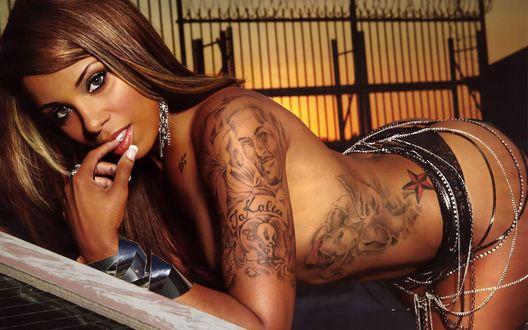 Обои Девушка с татуировками черных трусиках бижутерии на попе