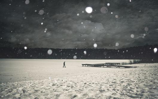 Обои Мужчина идет зимой по замерзшему озеру