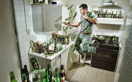 Обои Мужчина на кухне в вязаной безрукавке пытается поймать падающие пустые пивные бутылки, которыми заставлена вся кухня (dos equis)