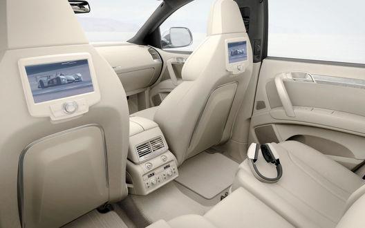 Обои Белый кожаный салон современного автомобиля, в кресла встроены небольшие экраны, на сидении лежат наушники