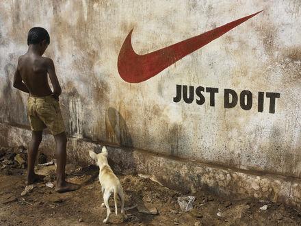 Обои Собака смотрит на писающего на стену с логотипом Найк / Nike мальчика (just doit - только по маленькому)