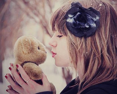 Обои Девушка целует плюшевого мишку