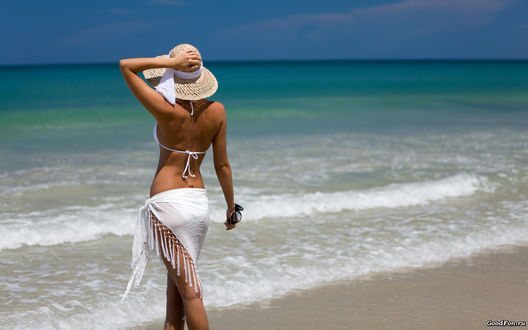 Обои Девушка в белоснежном купальнике и порэо придерживает соломеннуюшляпу на берегу моря