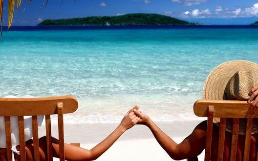 Обои Мужчина и девушка держатся за руки на берегу моря лежа в деревянных шезлонгах
