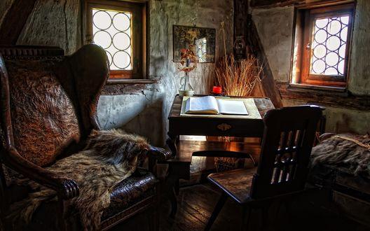 Обои Средневековая комната, два небольших окна кресло со звериной шкурой, стул и стойка для чтения книг