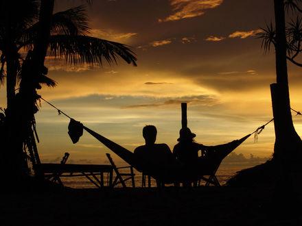 Обои Двое в гамаке на берегу моря во время заката