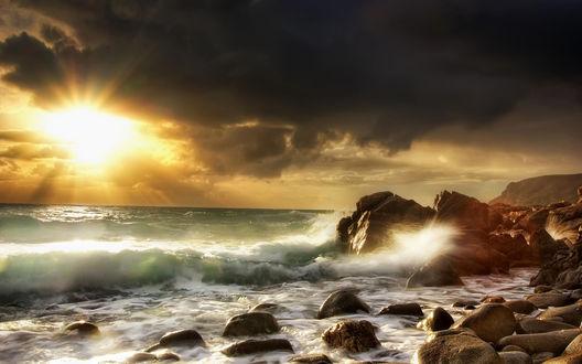 Обои На закате волны бьются о скалы