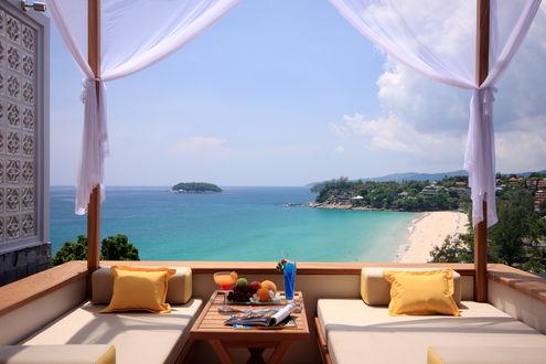 Обои Столик с фруктами, желтые подушки, вид из номера отеля на морское побережье