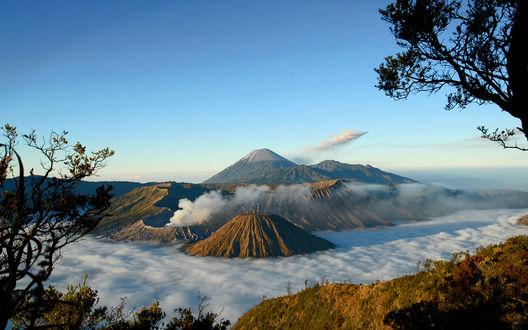 Обои Долина вулканов возвышающихся над облаками