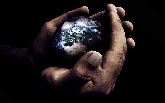 Обои Мужчина держит в руках планету Земля