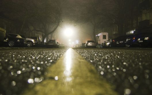 Обои Дождь в городе на дороге вдоль которой стоят припаркованные машины