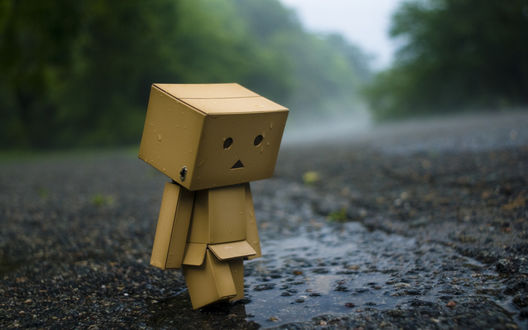 Обои Смешной робот, сделанный из коробок, шагает под дождём