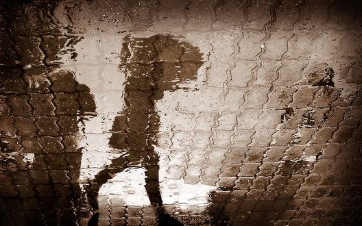 Обои Девушка с зонтом быстро идёт по городу, в луже мы видим её отражение