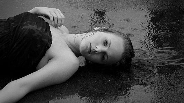Обои Грустная девушка лежит на асфальте под дождем