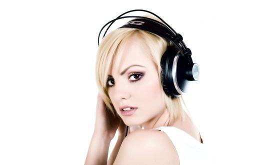 Обои Красивая блондинка слушает музыку в больших наушниках