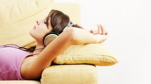 Обои Девушка в наушниках лежит на диване