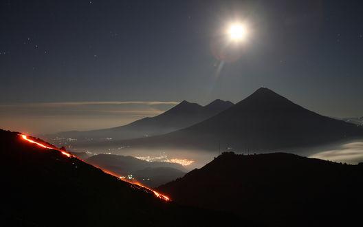 Обои Яркая луна над вершинами гор, вид на шоссе с огнями машин и город в долине