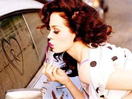 Обои Рыжая девушка красит губы возле машины на пыльном стекле которой нарисовано сердце вокруг букву R