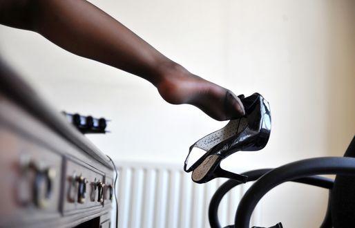Обои Женская ножка в чулках свисает со стола, с черной туфлей на длинном каблуке