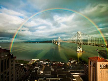 Обои Радуга необыкновенной красоты раскинулась над заливом прямо через мост
