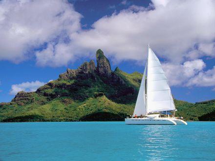 Обои Красивая белая яхта стоит на море у гористого острова