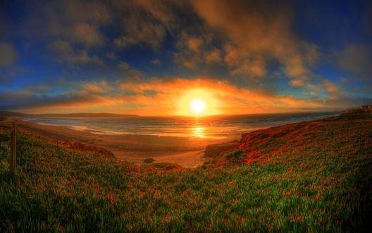 Обои Заходящее солнце освещает морское побережье