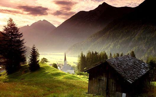 Обои В долине виднеется несколько домиков и небольшая церквушка
