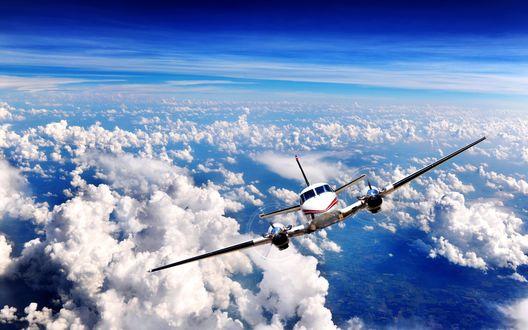 Обои Двухмоторный самолет летит над облаками