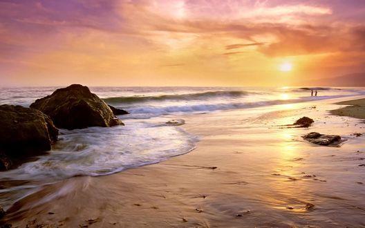 Обои Берег моря, усеянный большими камнями, вдали люди заходят в воду, пытаясь преодолеть большие волны и искупаться
