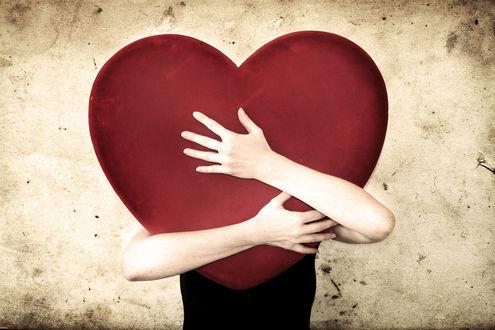 Обои Девушка обнимает большое сердце, видны только ее руки