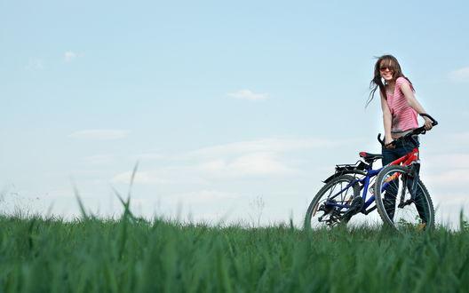 Обои Девушка держится, улыбаясь, за свой велосипед
