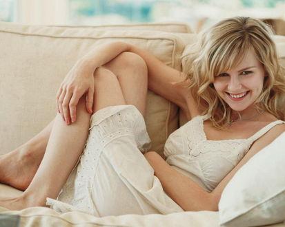 Обои Блондинка лежит на диване