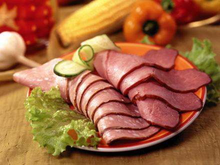 Обои Нарезанные пластинки ветчины и колбасы, рядом листья салата, паприка, чеснок и огурец