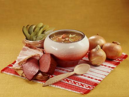 Обои Русская кухня - горшочек с солянкой, рядом продукты для её приготовления: репчатый лук, солёные огурцы и копчённости