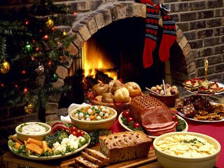 Обои Рождественский стол, на нём картофельный и другие салаты, выпечка, в том числе и специально приготовленные рождественские звёзды, тут и красивая, сочная ветчина и традиционные пикули и, конечно, праздничное убранство завершает наряженная ёлочка и камин