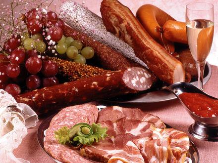 Обои Колбасы, копчёности, острый томатный соус, рядом фужер вина.Украшения в виде веточки с цветами и винограда