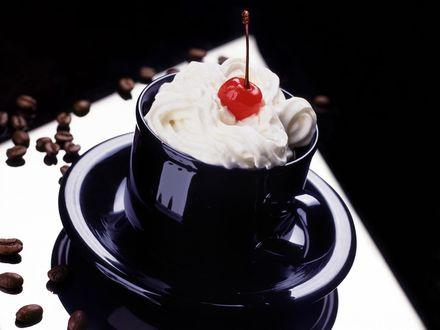 Обои Чашка с кремом в ней и вишенкой с разбросанными вокруг зёрнышками кофе