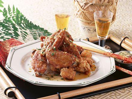Обои Куриные крылышки в кляре на подносе с палочкой и рисовой водкой в глиняном кувшине