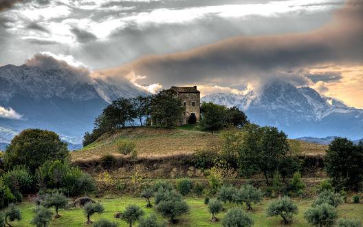 Обои Заброшенный дом на холме на фоне заснеженных гор, вершины которых утопают в проплывающих облаках