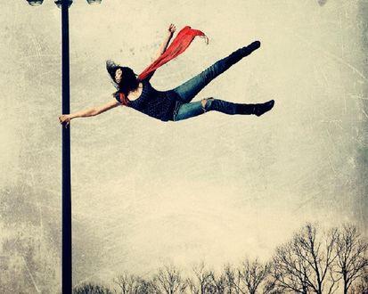 Обои Худенькую девушку уносит ветром, она зацепилась за фонарный столб